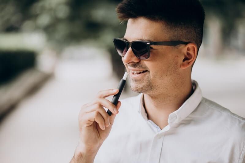 E sigara kullanan genç adam